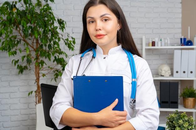 Jonge donkerbruine vrouw arts die zich met klembord in haar bureau bevindt