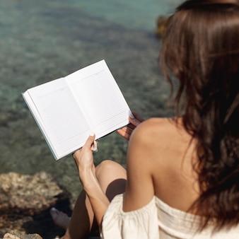 Jonge donkerbruine vrouw die een boek houdt