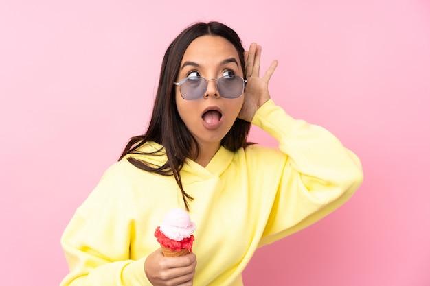 Jonge donkerbruine vrouw die een cornetroomijs op geïsoleerde roze houdt die aan iets luistert door hand op het oor te leggen