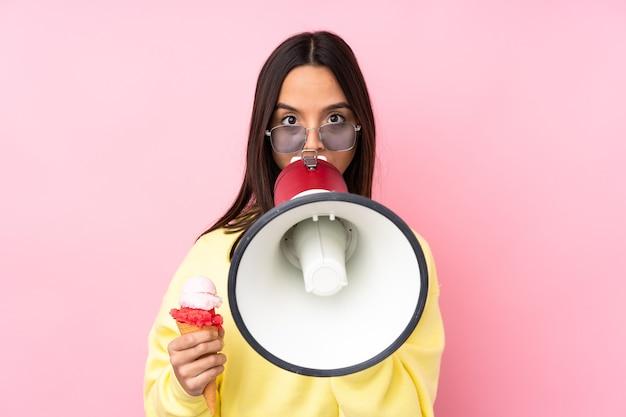 Jonge donkerbruine vrouw die een cornetroomijs op geïsoleerde roze houdt die door een megafoon schreeuwt