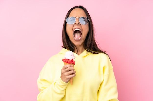 Jonge donkerbruine vrouw die een cornetroomijs op geïsoleerde roze houdt die naar voren met wijd open mond schreeuwt
