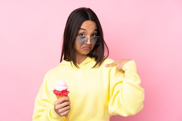 Jonge donkerbruine vrouw die een cornetroomijs op geïsoleerde roze houdt trots en zelfvoldaan