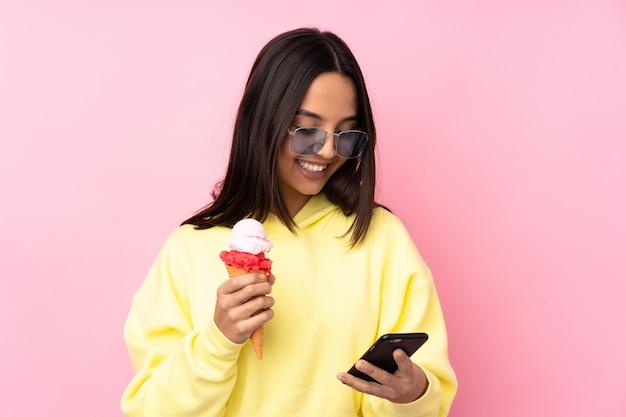 Jonge donkerbruine vrouw die een cornetroomijs over de geïsoleerde roze weg te nemen koffie van de muurholding en mobiel houdt