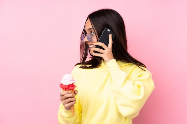 Jonge donkerbruine vrouw die een cornetroomijs over geïsoleerde roze muur houdt die een gesprek met de mobiele telefoon met iemand houdt
