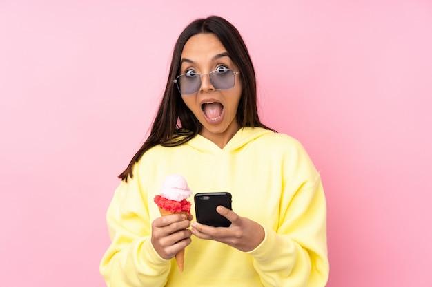 Jonge donkerbruine vrouw die een cornetroomijs over geïsoleerde roze muur houdt verrast en een bericht verzendt