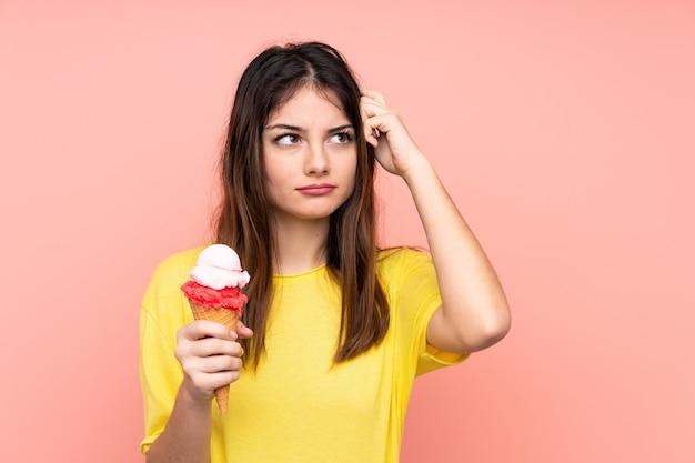 Jonge donkerbruine vrouw die een cornetroomijs over roze muur houdt die twijfels en met verwarde uitdrukking heeft