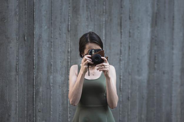 Jonge donkerbruine vrouw die een foto neemt