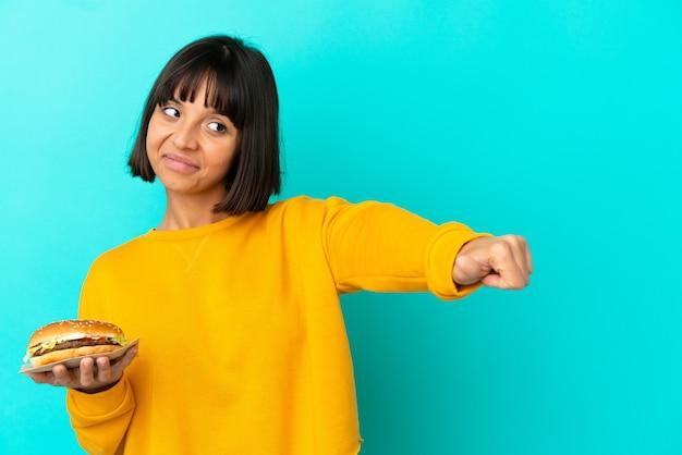 Jonge donkerbruine vrouw die een hamburger over geïsoleerde achtergrond houdt die een duim omhoog gebaar geeft