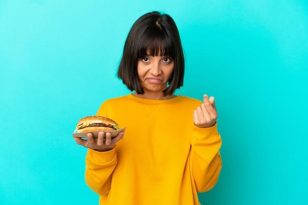 Jonge donkerbruine vrouw die een hamburger over geïsoleerde achtergrond houdt die geldgebaar maakt