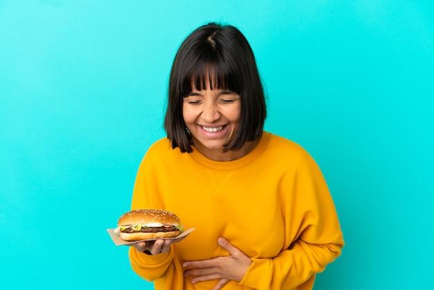 Jonge donkerbruine vrouw die een hamburger over geïsoleerde achtergrond houdt die veel glimlacht