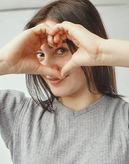Jonge donkerbruine vrouw die een hart met haar handen vormt