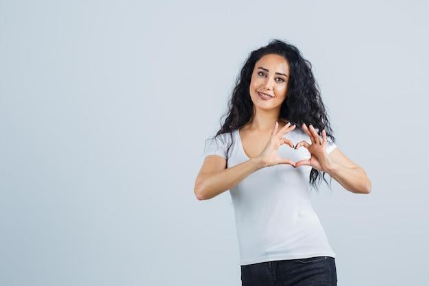 Jonge donkerbruine vrouw die een hart toont