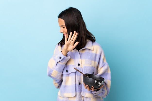 Jonge donkerbruine vrouw die een komhoogtepunt van noedels over geïsoleerde blauwe zenuwachtige het uitrekken zich handen aan de voorzijde houdt