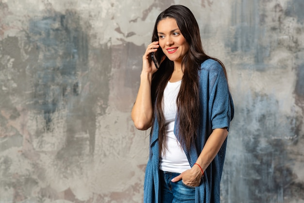 Jonge donkerbruine vrouw die een mobiele telefoon spreekt die zich tegen abstracte achtergrond bevindt.