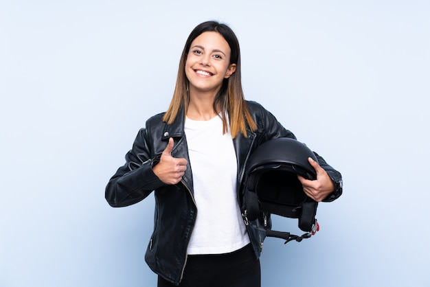 Jonge donkerbruine vrouw die een motorfietshelm over blauwe muur met omhoog duimen houdt