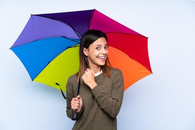 Jonge donkerbruine vrouw die een paraplu over blauwe muur houdt die een overwinning viert