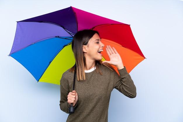 Jonge donkerbruine vrouw die een paraplu over blauwe muur houdt die met wijd open mond schreeuwt