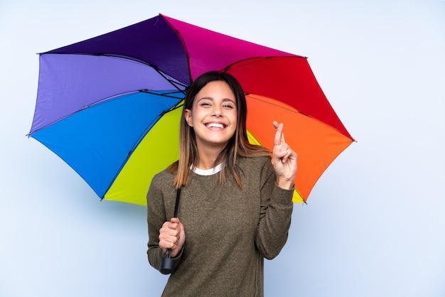Jonge donkerbruine vrouw die een paraplu over blauwe muur met vingers het kruisen houdt