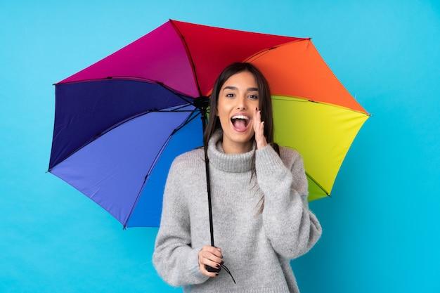 Jonge donkerbruine vrouw die een paraplu over geïsoleerde blauwe muur houdt die met wijd open mond schreeuwt