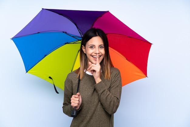 Jonge donkerbruine vrouw die een paraplu over geïsoleerde blauwe muur houdt die stiltegebaar doet