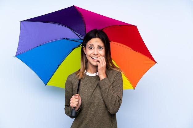 Jonge donkerbruine vrouw die een paraplu over geïsoleerde blauwe zenuwachtig en doen schrikken muur houden