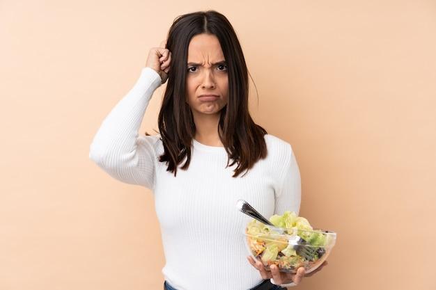 Jonge donkerbruine vrouw die een salade over geïsoleerde muur houdt die twijfels heeft