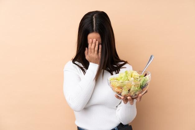 Jonge donkerbruine vrouw die een salade over geïsoleerde muur met vermoeide en zieke uitdrukking houdt