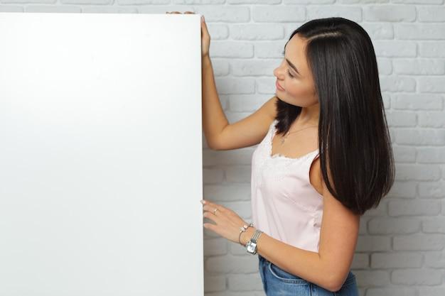 Jonge donkerbruine vrouw die grote lege witte raad met exemplaarruimte houdt