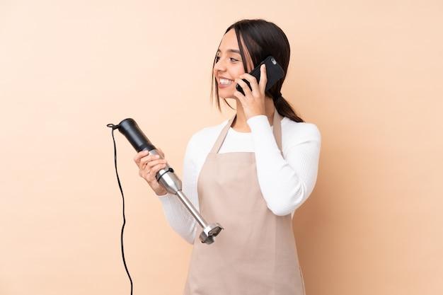Jonge donkerbruine vrouw die handmixer gebruikt die een gesprek met de mobiele telefoon met iemand houdt