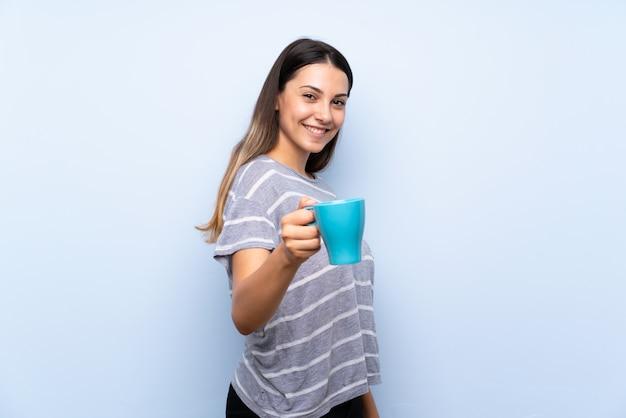 Jonge donkerbruine vrouw die hete kop van koffie houdt