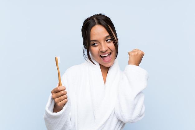Jonge donkerbruine vrouw die in badjas haar tanden borstelt die een overwinning vieren