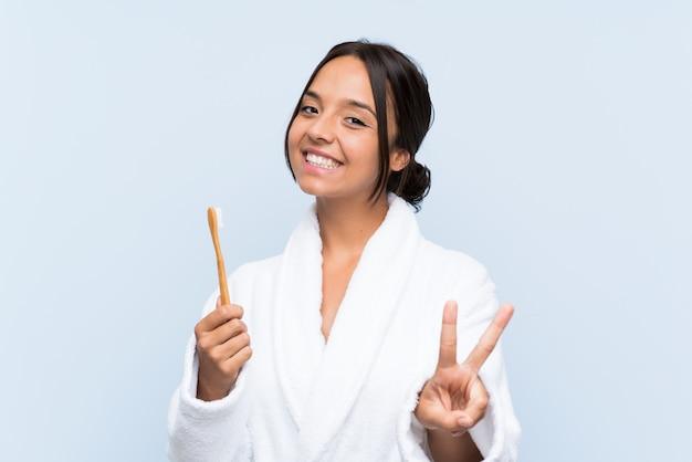 Jonge donkerbruine vrouw die in badjas haar tanden borstelt die en overwinningsteken glimlacht toont