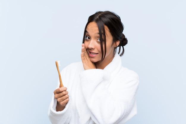 Jonge donkerbruine vrouw die in badjas haar tanden borstelt die iets fluistert