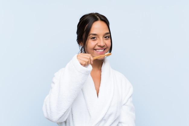 Jonge donkerbruine vrouw die in badjas haar tanden borstelt