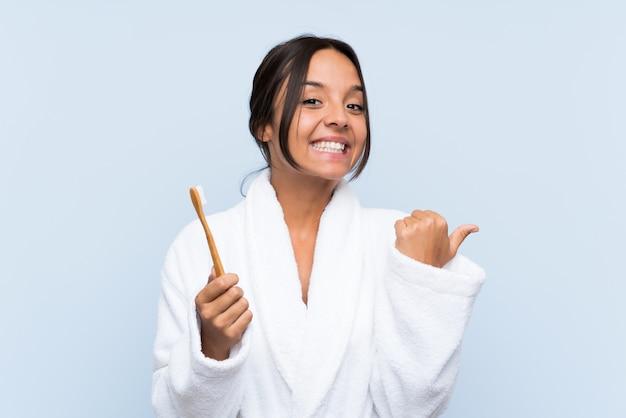 Jonge donkerbruine vrouw die in badjas haar tanden over geïsoleerde blauwe achtergrond borstelt die aan de kant richt om een product te voorstellen