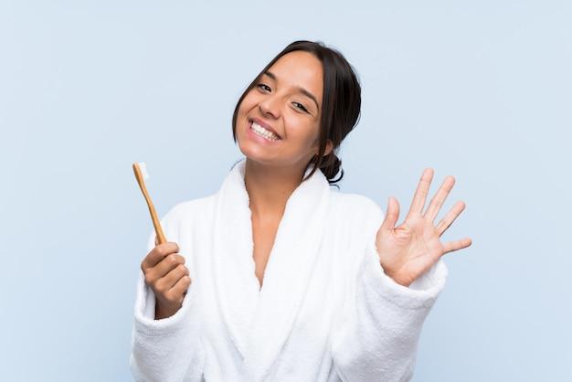 Jonge donkerbruine vrouw die in badjas haar tanden over het geïsoleerde blauwe achtergrond borstelen groeten met hand met gelukkige uitdrukking