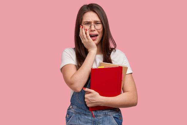 Jonge donkerbruine vrouw die in denimoveralls blocnotes houdt