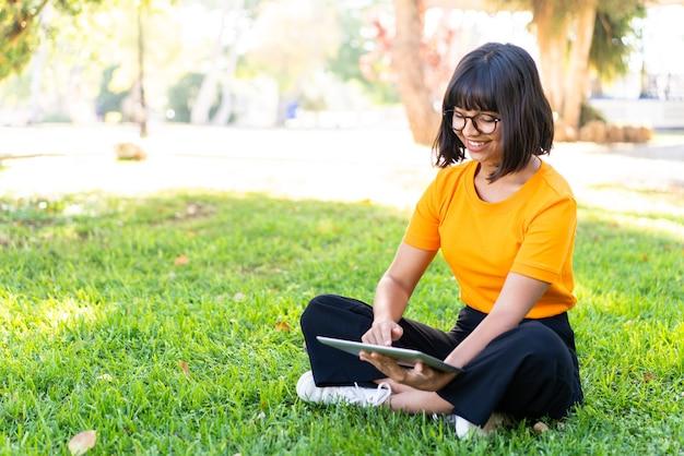 Jonge donkerbruine vrouw die in openlucht een tablet houdt