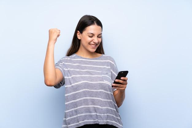 Jonge donkerbruine vrouw die mobiele telefoon met behulp van