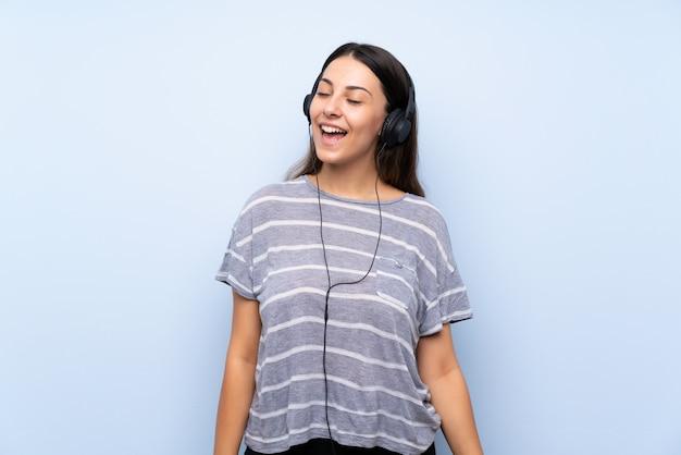 Jonge donkerbruine vrouw die over blauwe muur aan muziek met hoofdtelefoons luistert