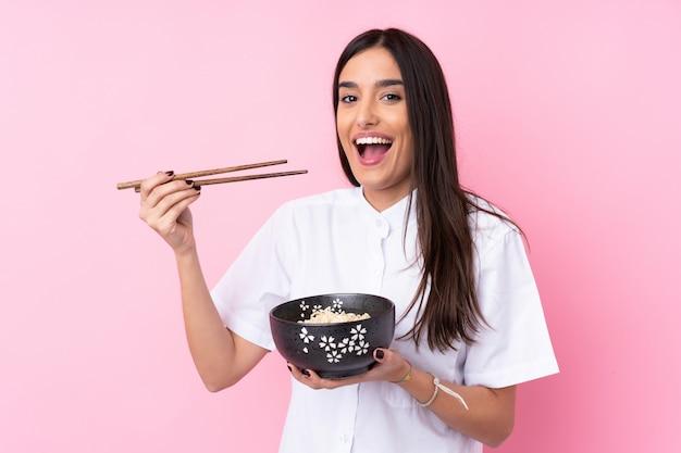 Jonge donkerbruine vrouw die over roze een kom van noedels met eetstokjes houdt