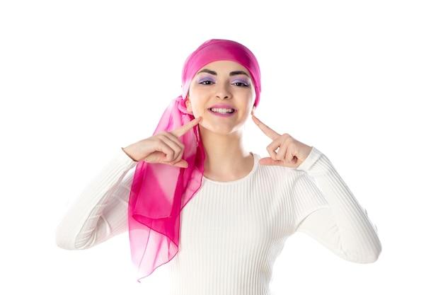 Jonge donkerbruine vrouw die roze geïsoleerde hoofddoek draagt