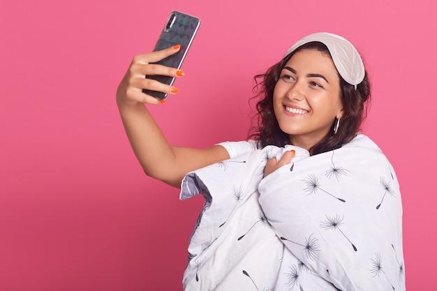 Jonge donkerbruine vrouw die slaapmasker draagt en witte deken verpakt, selfie tijdens bedtijd neemt, meisje dat pret in ochtend heeft