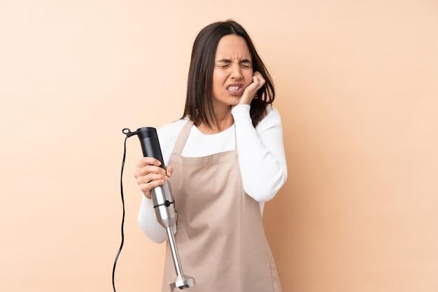 Jonge donkerbruine vrouw die staafmixer met tandpijn gebruikt