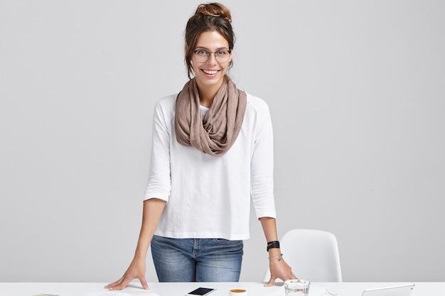 Jonge donkerbruine vrouw die zich dichtbij bureau bevindt