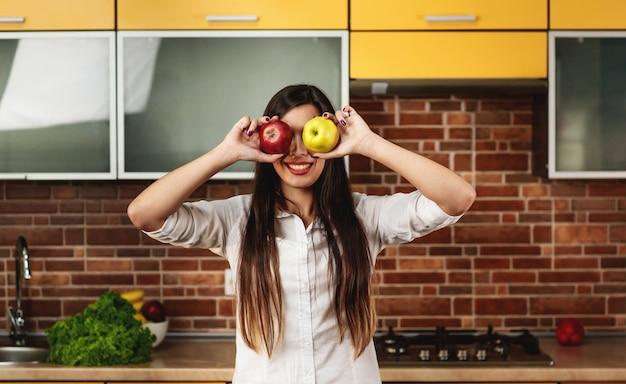 Jonge donkerbruine vrouw in de keuken die zijn ogen met twee appelen sluit, rood en geel. gezond eten en dieet concept. mooie vrouw met appels