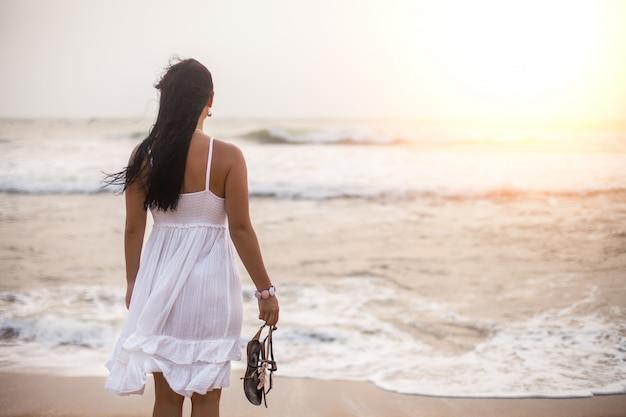Jonge donkerbruine vrouw in de zomer witte kleding die zich op strand bevindt en aan het overzees kijkt. meisje ontspannen op vakantie