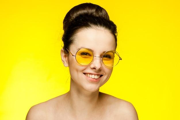 Jonge donkerbruine vrouw in gele glazen, portret