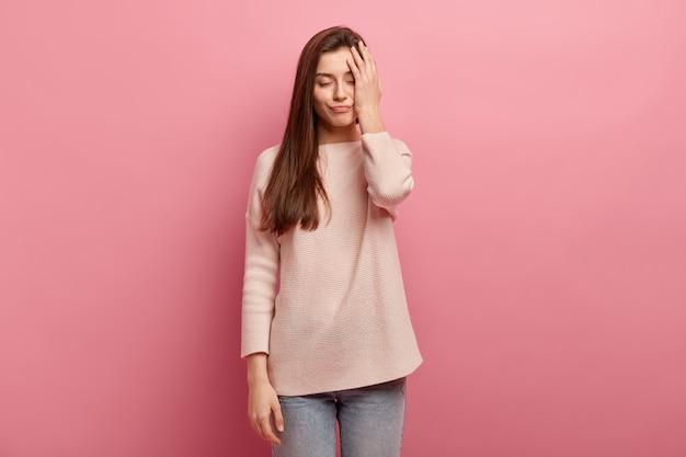 Jonge donkerbruine vrouw in jeans en sweater
