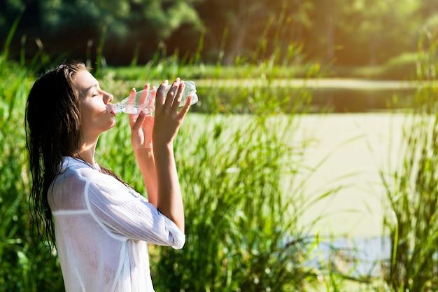 Jonge donkerbruine vrouw in witte kleding die en zich van fles op de zomerdag bevindt drinkt